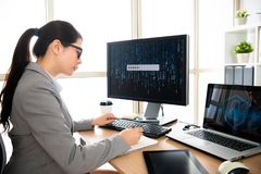 Female staff is writing while log in. Female staff in personal information safety company is sitting at her office desk and writing on notebook while log in stock images
