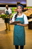 Female staff writing on notepad in super market. Portrait of female staff writing on notepad in super market Stock Photo