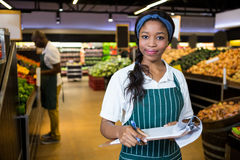 Female staff writing on notepad in super market Stock Photos