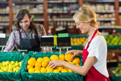 Female staffs checking fruits in organic section. Smiling female staffs checking fruits in organic section of supermarket Royalty Free Stock Photos