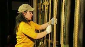 The female stage worker in gloves lifts the theater curtain and fastens the cable. The average plan stock video footage