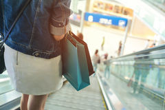 Female standing on escalator spending customer consumerism at de. Partment store Royalty Free Stock Photos