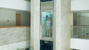 A female is standing in glass moving lift. A female is standing in glass transparent lift that is going up and down. Elevator makes the commute to higher floor stock video footage