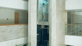 A female is standing in glass moving lift. A female is standing in glass transparent lift that is going up and down. Elevator makes the commute to higher floor stock footage