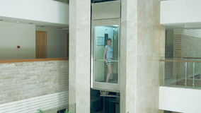 A female is standing in glass moving lift. A female is standing in glass transparent lift that is going up and down. Elevator makes the commute to higher floor stock video