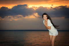 Female standing near ocean in rays of sunset Stock Photography