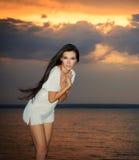 Female standing near ocean in rays of sunset. Pretty female standing near ocean in rays of sunset Stock Image