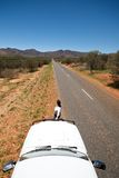 Female standing next to car looking down road. Long road in outback with person standing nexy to car Stock Photography