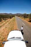 Female standing next to car with road behind. Long road in outback with person standing nexy to car Royalty Free Stock Photography