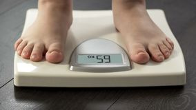 Female standing on scales to see weight control result, healthy dieting, frontal. Stock photo royalty free stock image
