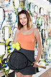 Female standing in sporting goods store with balls and racket Royalty Free Stock Photo