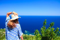 Female staring at the sea from a hill, while holding her hat with her left hand. Shot during daytime in summer stock photo