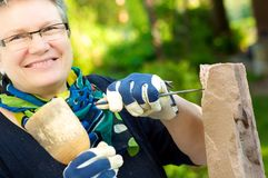 Female stonemason. Laughs into the camera at work Royalty Free Stock Photography