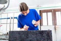 Female Stonemason applying inscription on tombstone. Stone carver applying ornament on headstone royalty free stock photography