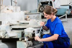 Stone mason chucking workpiece into polishing machine. Female stonemason chucking workpiece into polishing machine Royalty Free Stock Image