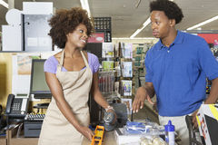 Female store clerk looking at customer while scanning product at super market stock photography