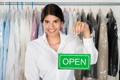 Female store owner with open sign board Royalty Free Stock Photography