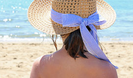 Female with straw hat beside the beautiful sea in summer Stock Photos