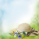Female straw hat with ribbon and bouquet of flowers on a gentle vintage background with space for text or photo Stock Photography