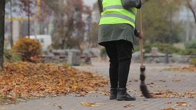 Female street cleaner sweeping autumn park, low-paid job, no prospects in life. Stock footage stock video