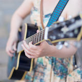 Female street musician playing guitar. Stock Photo