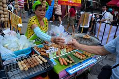 Female street vendor sells traditional sausages in market bazaar Chiang Mai Thailand. Chiang Mai, Thailand - July 17, 2016: A street vendor prepares and sells Stock Images