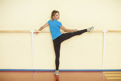 Female stretching in colorful fitness class with handrail. Female stretching in colorful fitness class with one leg on handrail royalty free stock image