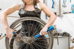 Female strong worker dismantling the chain of the bicycle. Strong craftswoman repairing the bicycle. Muscular athletic hardworking worker standing in the Stock Image