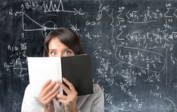 Female student. Young woman with book covering face and a blackboard on  the background Stock Photography