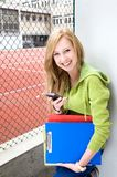 Female student. Teenage girl holding books and mobile phone Stock Images