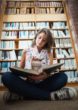 Female student against bookshelf reading a book on the library floor Stock Photos