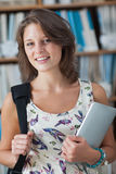 Female student against bookshelf with tablet PC and bag in library Stock Photography