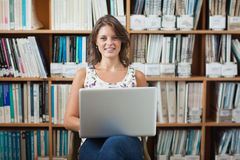 Female student against bookshelf using laptop in library Stock Photo