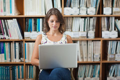 Female student against bookshelf using laptop in library Stock Photos