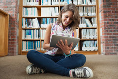 Female student against bookshelf using tablet PC on the library floor Stock Image