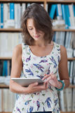 Female student against bookshelf using tablet PC in library Stock Photo