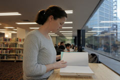 Female student reading a book in a library Royalty Free Stock Photos