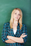 Female Student With Arms Crossed Standing Against Chalkboard Stock Image