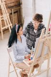 Female Student in Art Class. High agle portrait of smiling young women painting sitting by easel in art studio working with female art teacher in art class, copy stock photography