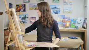 Young woman is learning to draw in artistic workshop, painting on canvas. Female student of art university is painting in class. She is standing in front of stock footage