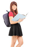Female student with backpack holding a book Stock Photos