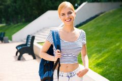Female student with backpack standing outdoors Stock Photos