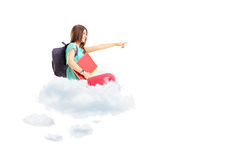 Female student with bag pointing with her hand and sitting on clouds Royalty Free Stock Photo