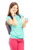 Female student with a bag talking on a phone and holding a credi Stock Images
