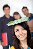 Female student with a book on top Royalty Free Stock Photo