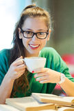 Female student with books and cup of coffee Royalty Free Stock Photos