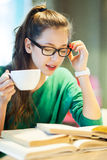 Female student with books and cup of coffee Royalty Free Stock Images