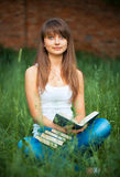 Female student with books on grass outdoors Royalty Free Stock Image