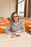 Female Student With Books Sitting In Classroom Stock Photos