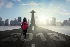 Student walking on the road with upward arrow Stock Image
